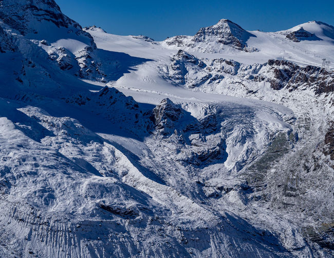 Scenic view of a glacier and snowcapped mountains against sky