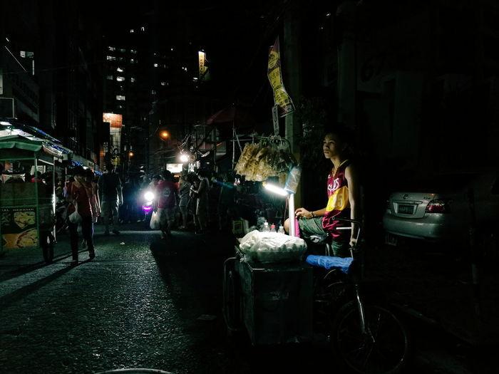 Woman on illuminated street at night