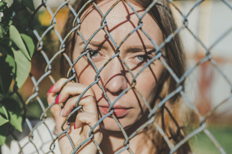 The face of a young girl behind a metal fence