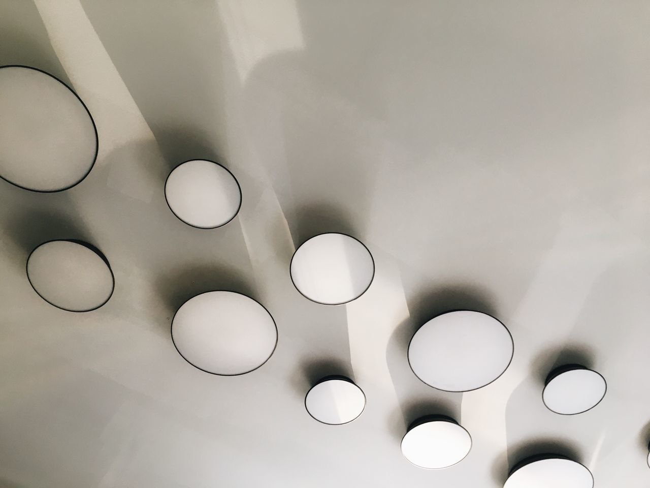 indoors, no people, circle, geometric shape, ceiling, illuminated, shape, white color, lighting equipment, pattern, backgrounds, close-up, design, full frame, technology, electricity, glowing, architecture, light, group of objects, directly below, electric lamp