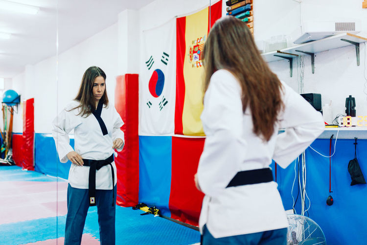 Young woman wearing martial arts dress while standing by mirror