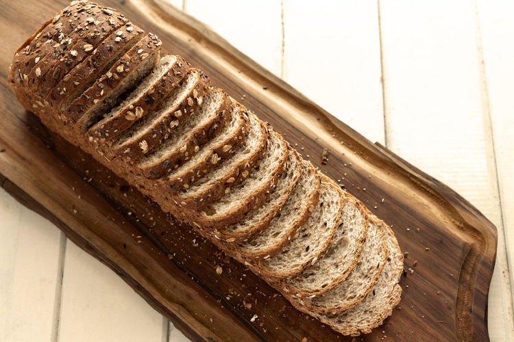 Sliced multigrain bread on cutting board. Diagonal, top view. Breakfast Diet Natural Wheat Bake Bakery Bread Brown Bread Close-up Crust Directly Above Food Food And Drink Grain Healthy Eating Loaf Loaf Of Bread Multigrainbread No People Sliced Sliced Bread Studio Photography Wholemeal Bread