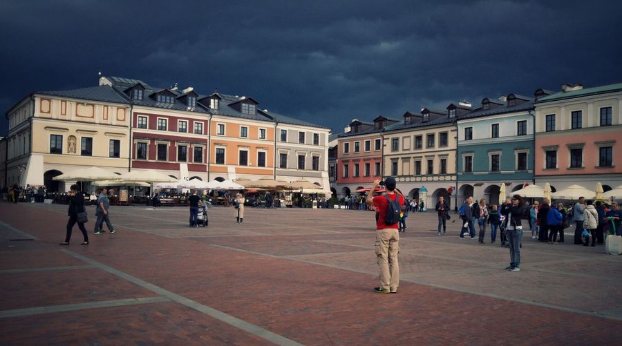 People walking at great market square against cloudy sky during stormy weather
