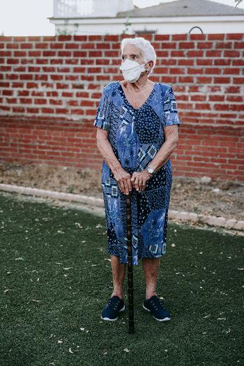 Full length of senior woman holding stick standing against brick wall