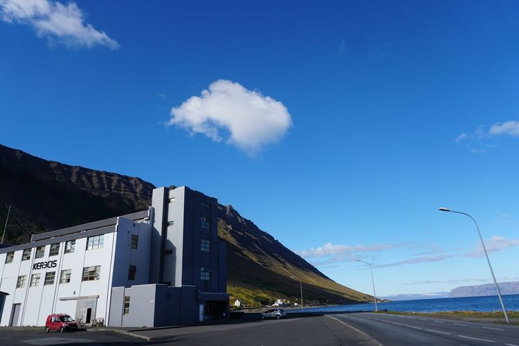 Road by mountain against blue sky