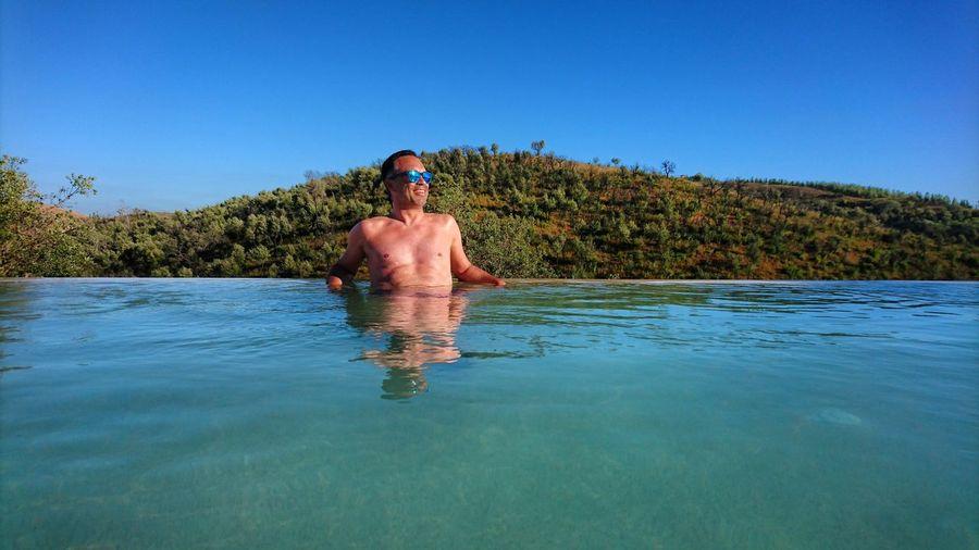 Smiling shirtless man in infinity pool looking away