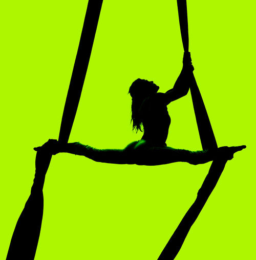Full length of silhouette woman performing acrobatic stunt on curtain against green background