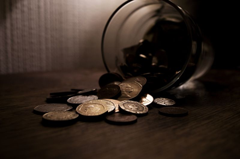 Close-up of coins spilling from jar on table