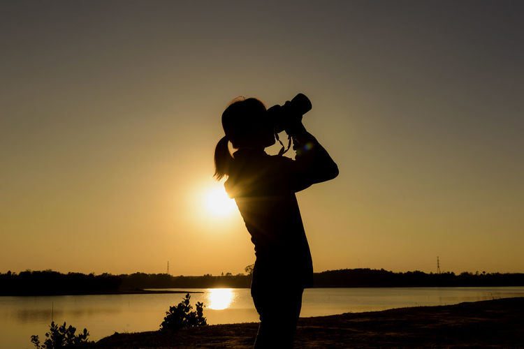 Silhouette man photographing lake against sky during sunset