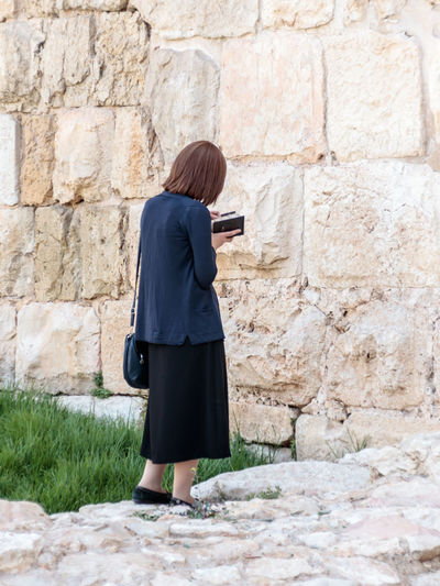 Rear view of woman standing against stone wall