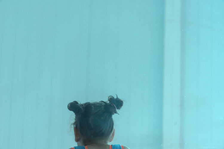 Rear view of woman looking at blue wall