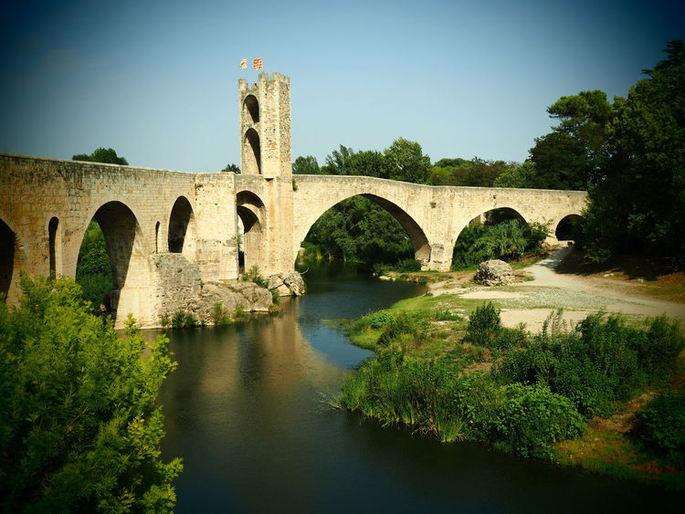 Landscape of the medieval village of Besalu in Girona, Spain Besalú Girona SPAIN Touristic Travel Arch Arch Bridge Architecture Bridge Bridge - Man Made Structure Built Structure Europe Landmark Landscape Medieval Nature Outdoors Picturesque River Tourism Tower Town Tree Village Water