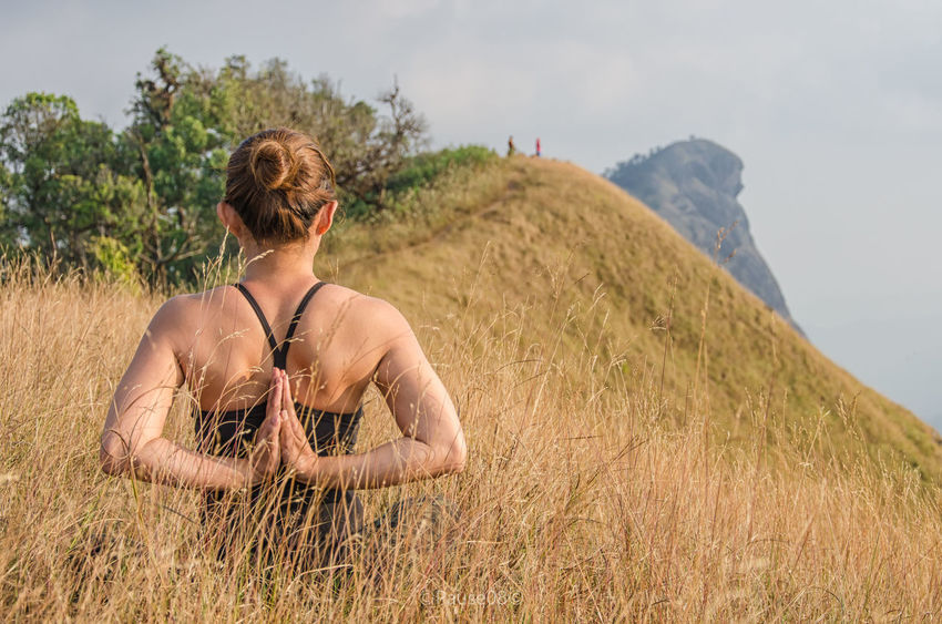 Young girl doing yoga on the mountain. Beauty In Nature Casual Clothing Day Field Grass Grassy Growth Landscape Leisure Activity Lifestyles Mountain Nature Non-urban Scene Outdoors Plant Remote Rural Scene Scenics Sky Tranquil Scene Tranquility