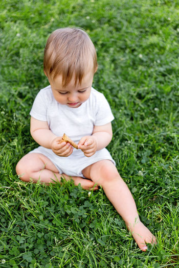 High angle view of baby girl sitting on grass