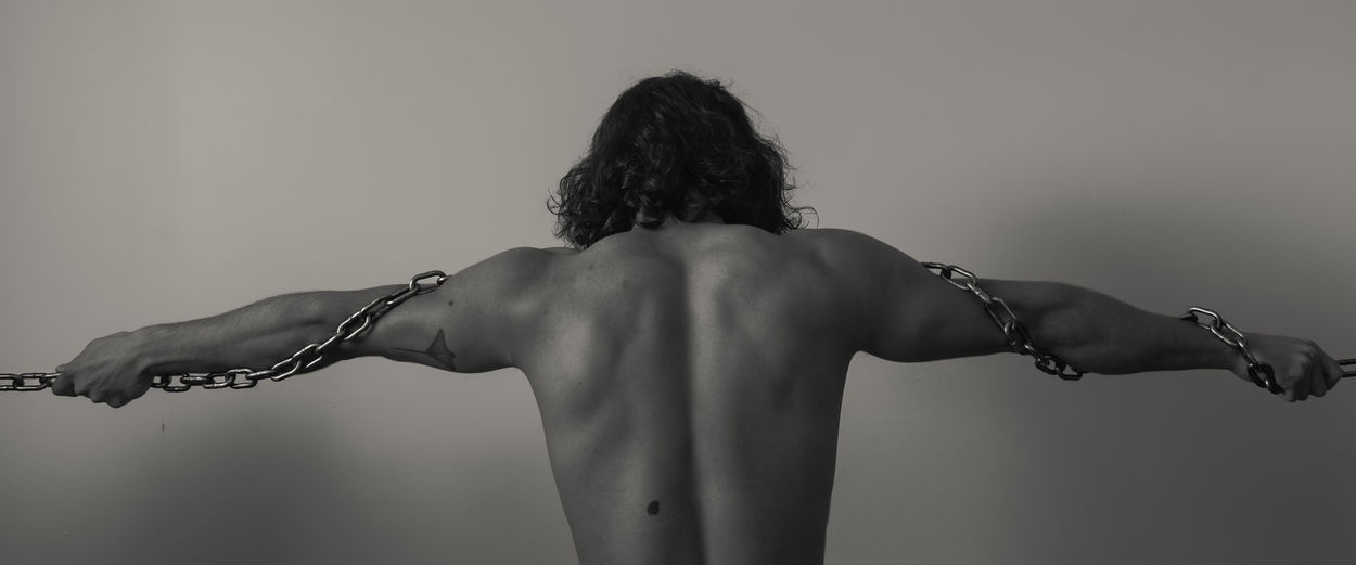 Rear view of a shirtless, chained man against white background