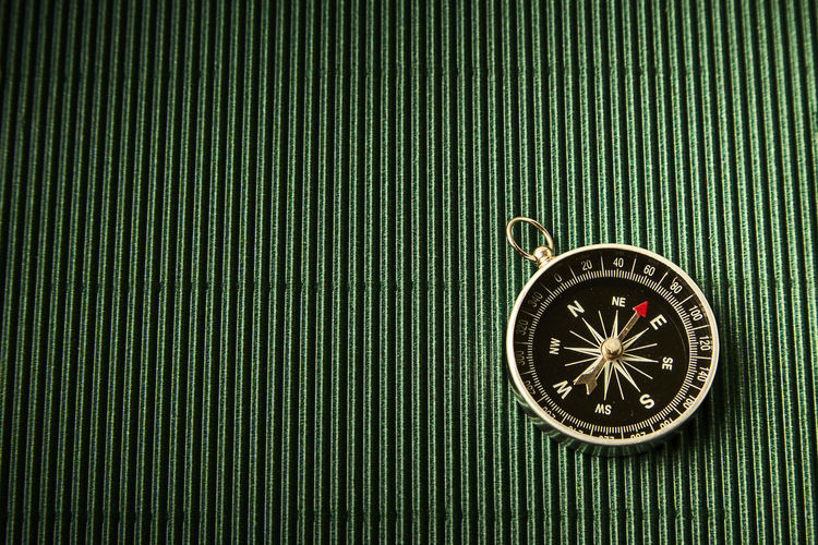 Close-Up Of Compass On Green Table
