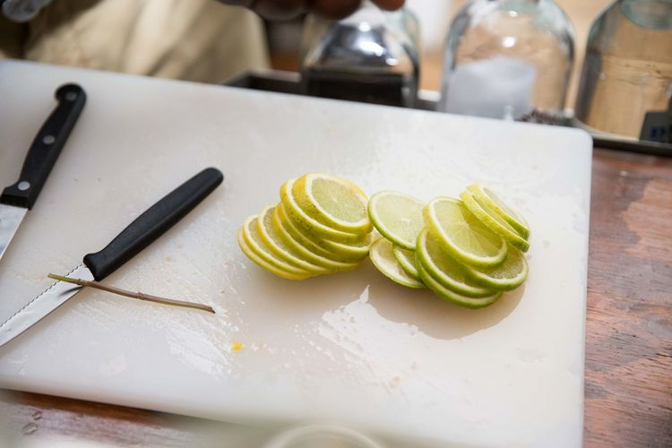 Lemon slice with knife on cutting board