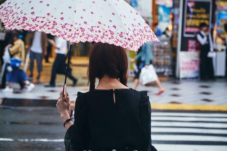 Rear view of woman holding umbrella during rainy season