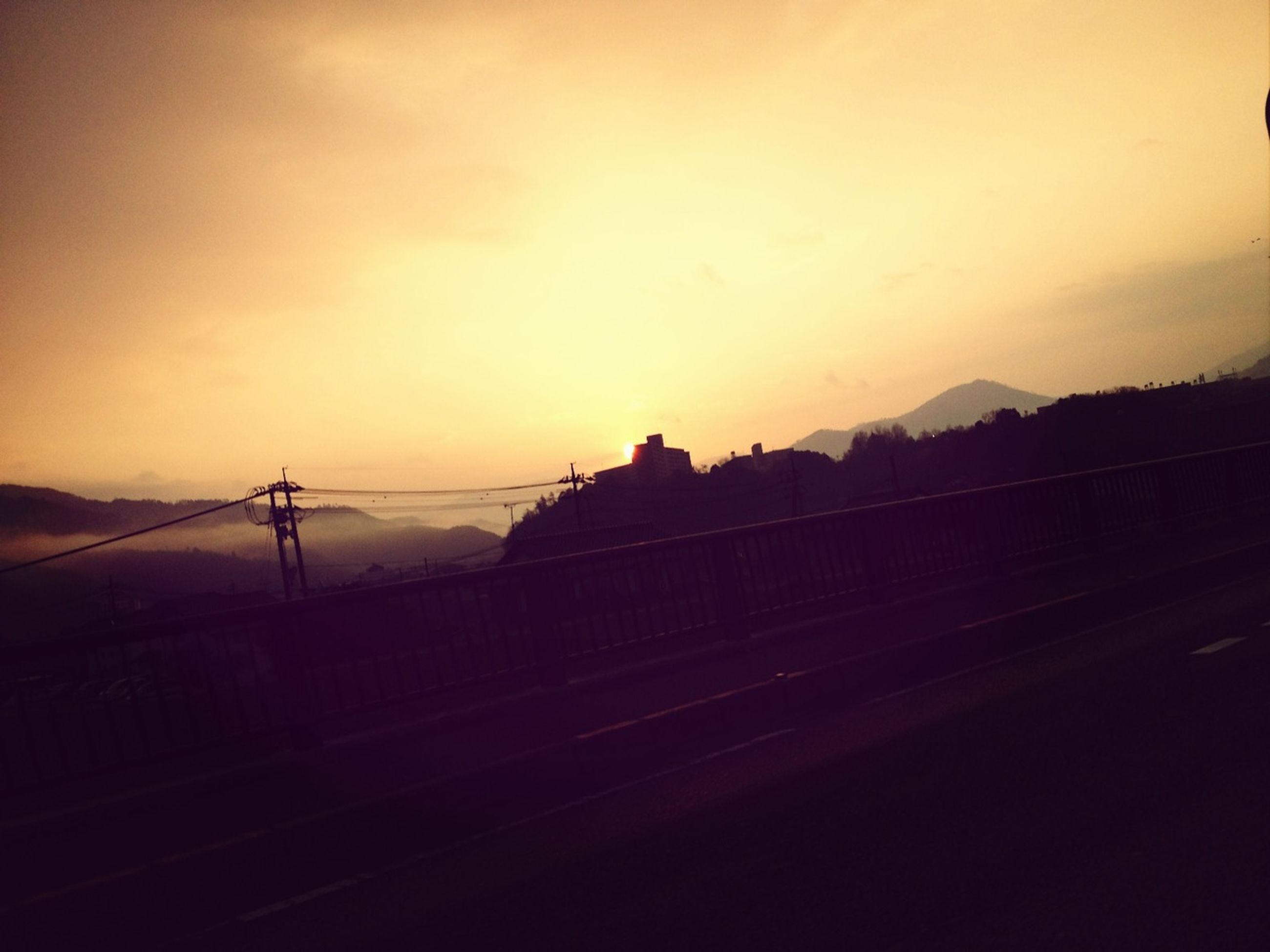 sunset, silhouette, sky, orange color, transportation, built structure, railing, dusk, connection, architecture, scenics, mountain, nature, beauty in nature, tranquility, dark, tranquil scene, outdoors, no people, cloud - sky