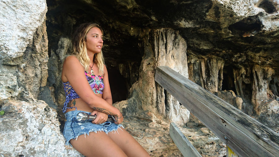 Thoughtful woman looking away while sitting by cave at cayman islands