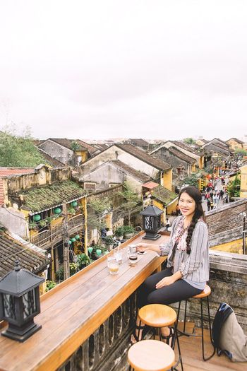 Portrait of woman sitting at cafe against houses