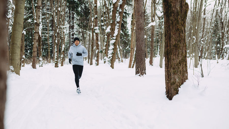 Man Running In Forest During Winter