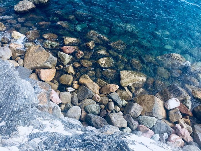 Summertime Summer Blue Wave Blue Water Solid Sea Nature Rock High Angle View Beach Day Land No People Stone - Object Sunlight Rock - Object Beauty In Nature Underwater Abundance Stone Outdoors Full Frame Pebble