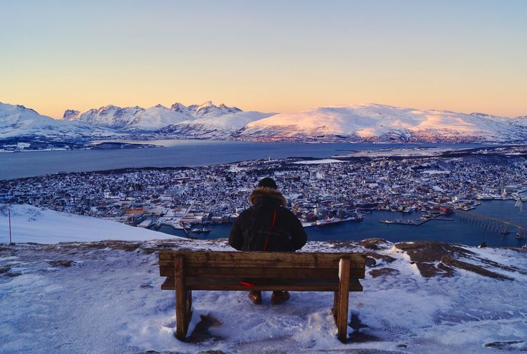 Rear View Of Man Sitting On Snowcapped Mountain Against Sky In City
