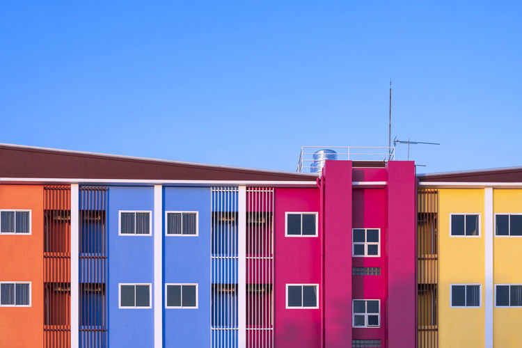 Multi colored residential buildings against clear blue sky