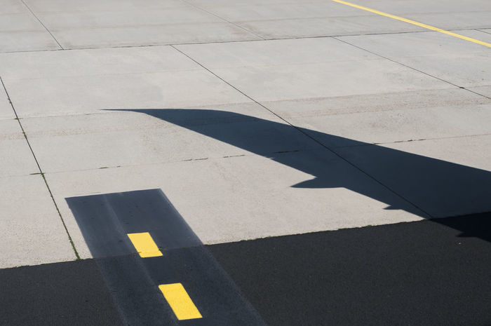 Shadow of the wing of an Airbus A321 on the taxi way. Wing Yellow Lines Aircraft Wing Airfield High Angle View No People Outdoors Road Marking Shadow Sunlight Taxi Way Taxiway