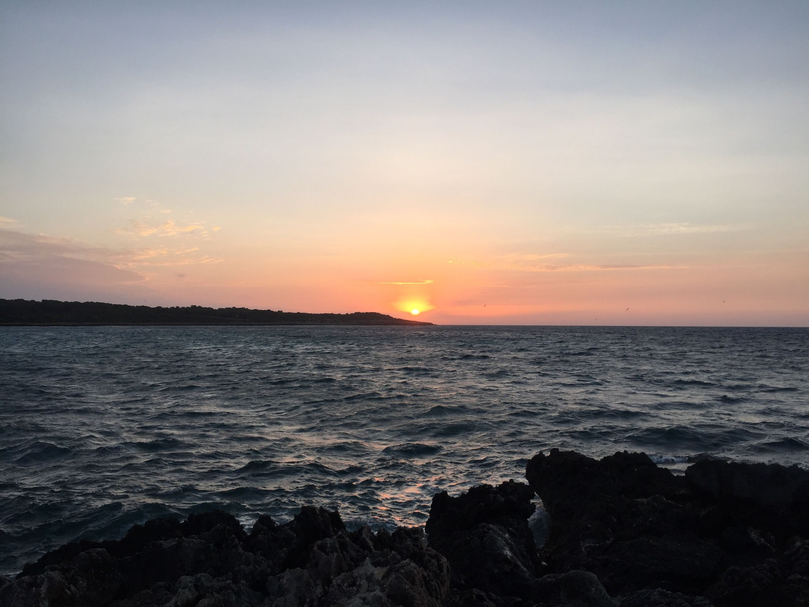 sunset, water, scenics, sun, tranquil scene, sea, tranquility, beauty in nature, rippled, idyllic, orange color, nature, sky, travel destinations, seascape, non-urban scene, tourism, vacations, majestic, remote, ocean, waterfront, calm, atmosphere, back lit, atmospheric mood, outdoors, moody sky, cloud - sky, wave