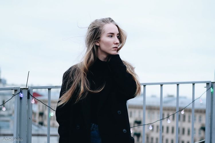 Portrait of beautiful woman standing by railing against sky