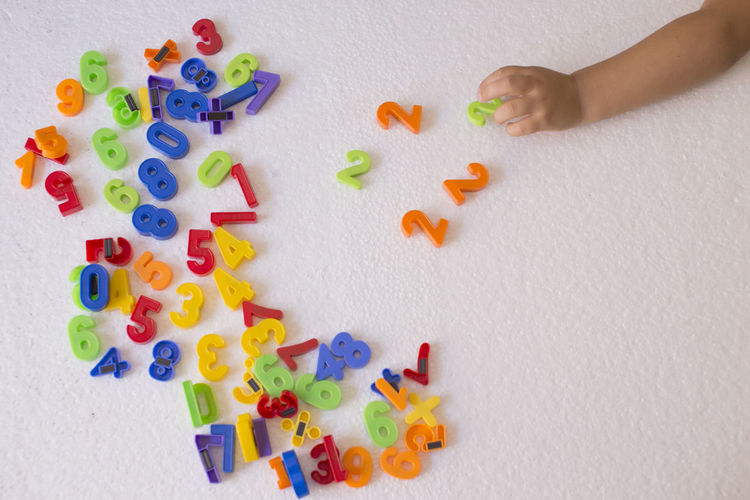 Body Part Child Childhood Choice Hand High Angle View Human Body Part Human Hand Indoors  Leisure Activity Multi Colored Numbers One Person Playing Studio Shot Toy Variation