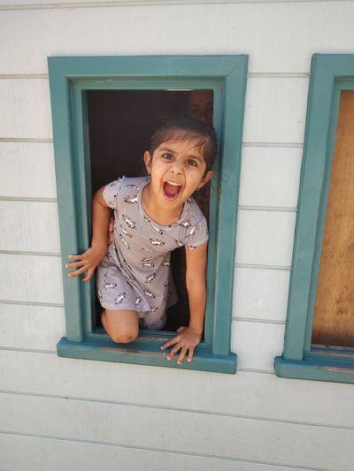 Portrait of girl screaming while kneeling on window