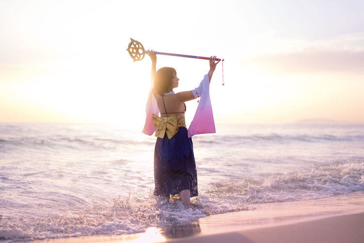 Young woman wearing costume holding wand at beach during sunset