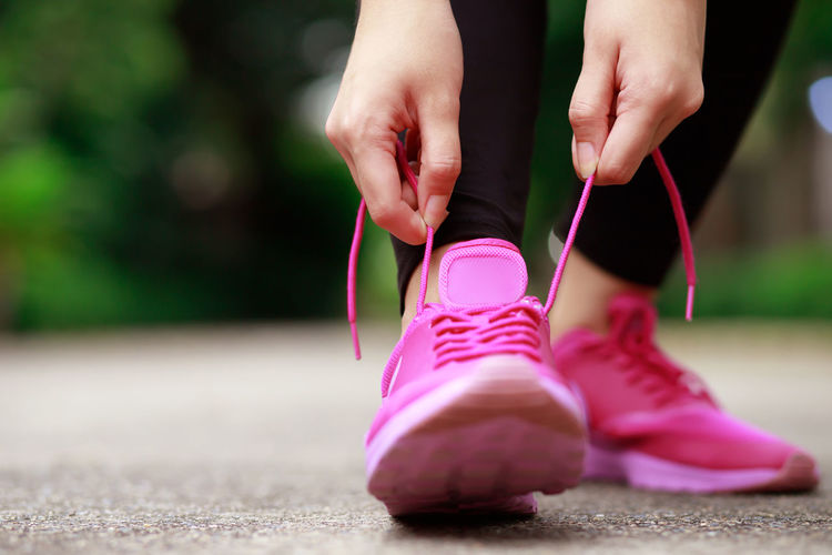 Low section of woman wearing pink shoes