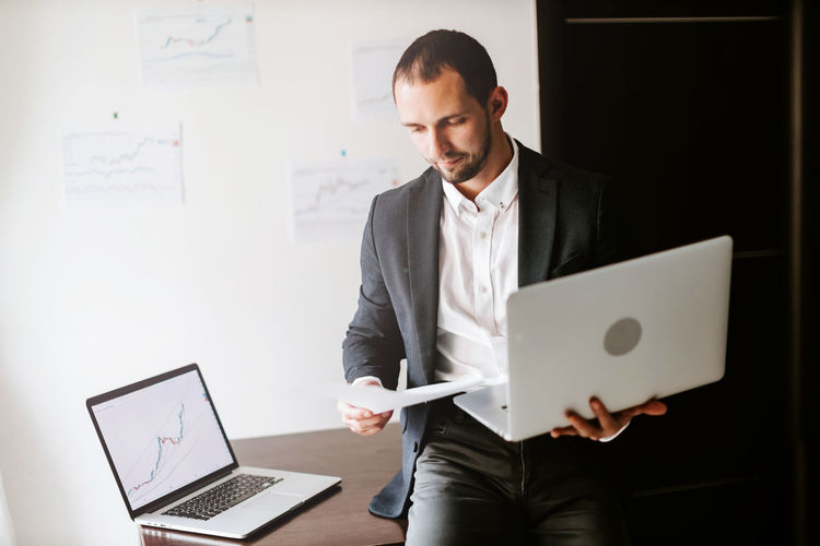 Businessman holding laptop at office