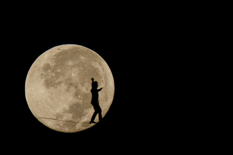 Silhouette man against moon at night