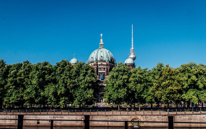 Berlin cathedral by trees against clear blue sky
