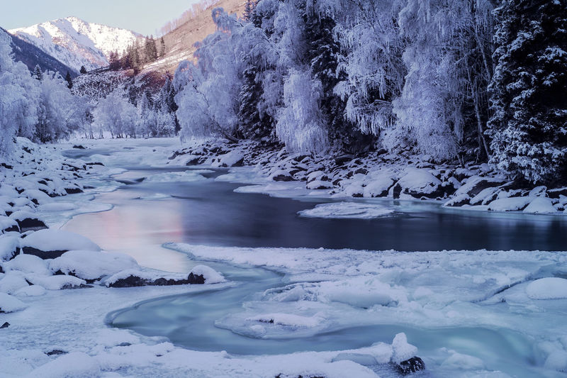 Snow covered river against mountain