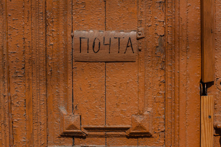 Close-Up Of Nameplate On Brown Wooden Door