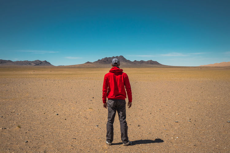 One Person Scenics - Nature Sky Desert Land Beauty In Nature Standing Environment Arid Climate Real People Full Length Landscape Sunlight Rear View Nature Tranquil Scene Day Climate Blue Tranquility Outdoors The Portraitist - 2019 EyeEm Awards The Traveler - 2019 EyeEm Awards