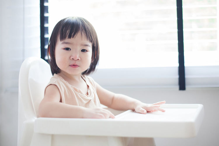 Portrait of cute baby girl sitting on high chair against window at home