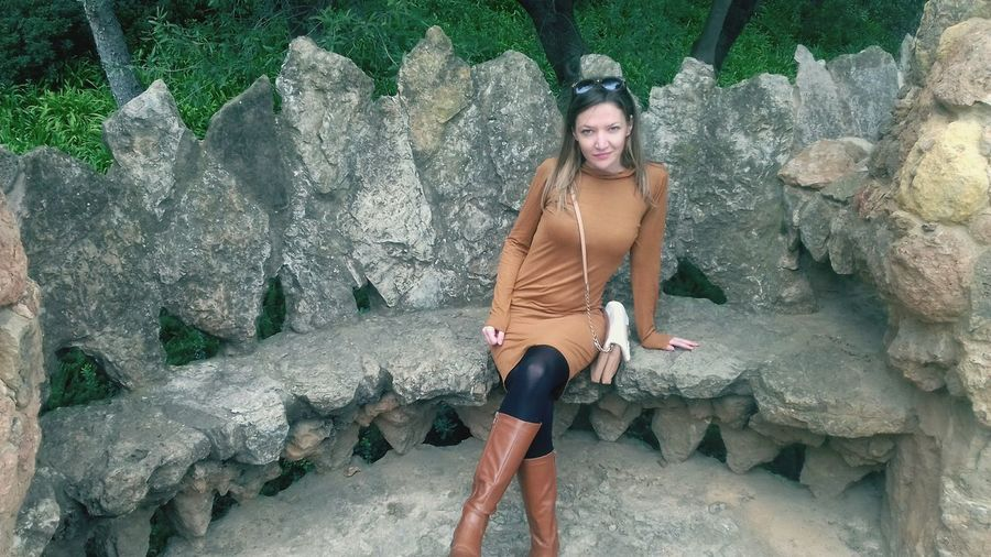 Full Length Portrait Of Beautiful Woman Sitting On Stone Seat At Park Guell