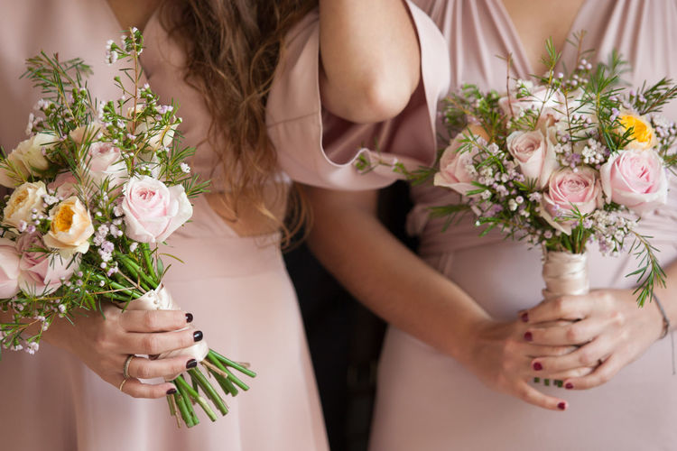 Midsection of women holding bouquets