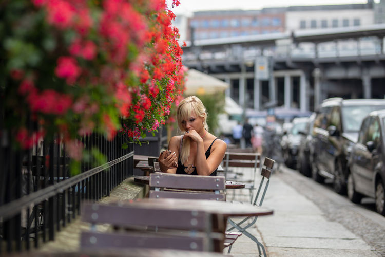 Young woman sitting at sidewalk cafe in city