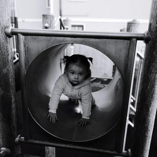 Portrait of cute baby girl in slide tunnel