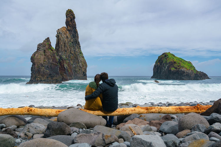Janela Islets in Porto Moniz in Madeira with a couple sitted on a yellow tree on the ground Madeira Portugal Island Ilha Travel Landscape Nature Mountain Yellow Tree Outdoors Beach Porto Moniz Ribeira Da Janela Islet Panorama Panoramic Seascape Sea Europe Waves Couple Romantic Valentine Romance
