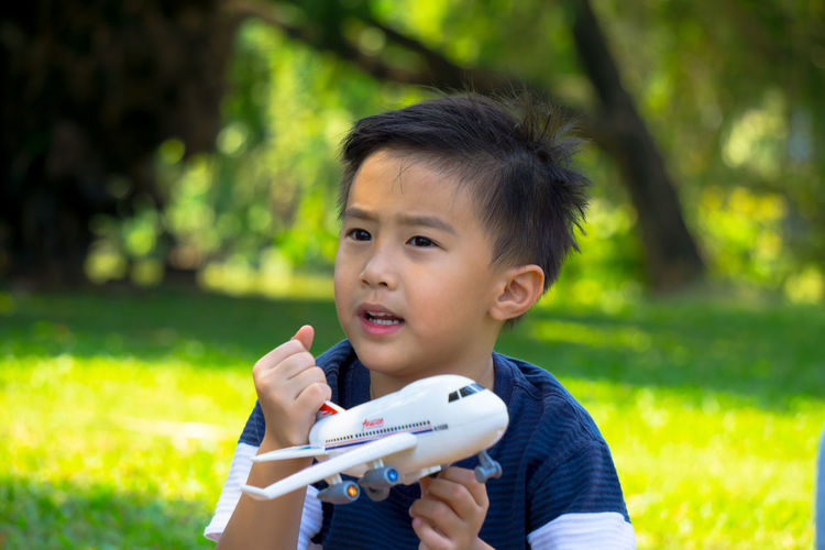 A boy playing with airplane dreams of pilot aviator traveling in nature park background Boys Childhood Close-up Day Elementary Age Focus On Foreground Grass Growth Holding Leisure Activity Lifestyles Nature One Person Outdoors Park - Man Made Space People Portrait Real People Technology Tree