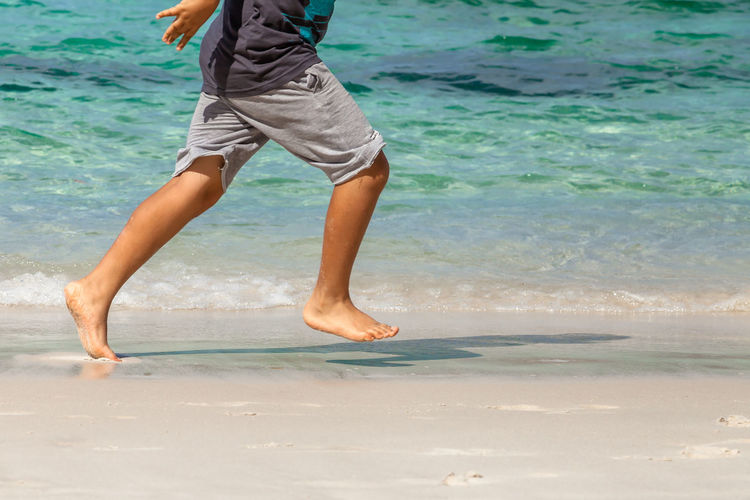 Low Section Of Boy Running On Shore At Beach During Sunny Day